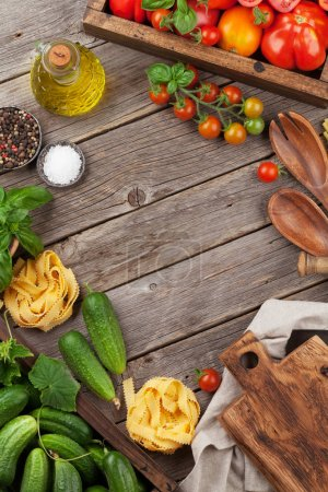 Photo for Fresh garden tomatoes and cucumbers with herbs cooking on wooden table. Top view with space for your text - Royalty Free Image