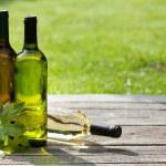 White wine bottles on wooden table. Outdoor still ...