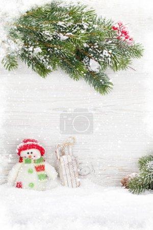 Photo pour Jouets de Noël bonhomme de neige et luge et branche de sapin. Découvre avec espace copie - image libre de droit