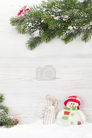 Christmas snowman and sledge toys and fir tree branch. Xmas backdrop with copy space