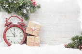 Christmas gift boxes, alarm clock and fir tree branch covered by snow in front of wooden wall. View with copy space