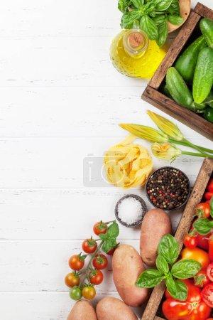Photo pour Tomates fraîches de jardin, concombres et pâtes sur la table de cuisson. Vue de dessus avec espace pour votre texte - image libre de droit
