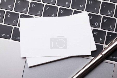 Blank business cards over laptop keyboard. Top view with space for your text
