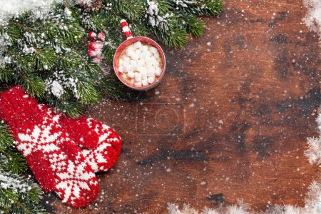 Photo for Christmas card with mittens, cup of hot chocolate with marshmallow and fir tree branch covered by snow on wooden background. Top view xmas backdrop with space for your greetings - Royalty Free Image