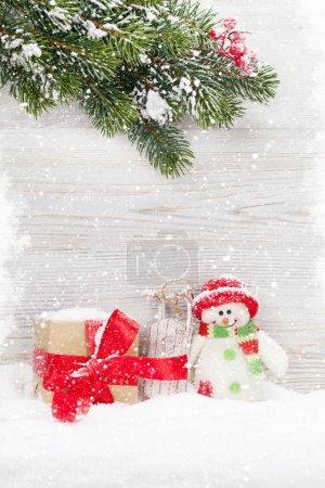 Photo pour Jouet de Noël bonhomme de neige, branche d'arbre de boîte et le sapin cadeau. Carte de voeux de Noël avec un espace pour vos voeux - image libre de droit