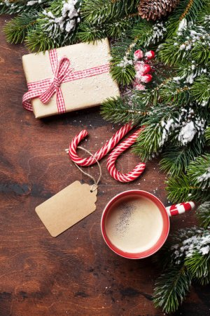 Photo for Christmas gift box, candy canes, cup of hot chocolate with marshmallow and fir tree branch covered by snow on wooden background. Top view xmas backdrop with space for your greetings - Royalty Free Image