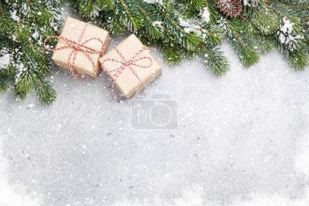 Photo pour Coffrets cadeaux de Noël et branche de sapin recouverte de neige sur fond de pierre. Fond de Noël vue de dessus avec de l'espace pour vos salutations - image libre de droit