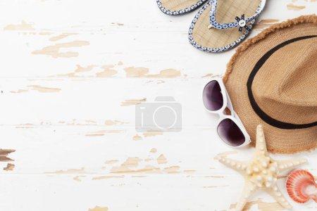 Foto de Concepto de fondo de vacaciones con gorra, gafas de sol, chanclas y conchas de viaje sobre fondo de madera. Vista superior con espacio de copia. Endecha plana - Imagen libre de derechos