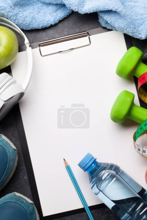 Photo for Dumbbells, sneakers, headphones and apple on stone background - Royalty Free Image