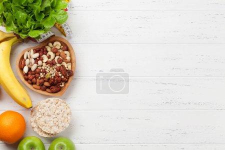Photo pour Nourriture saine et concept de fitness. Diverses noix, fruits, céréales et salade. Pose plate avec espace de copie pour votre texte - image libre de droit