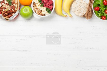 Photo for Healthy food and fitness concept. Salad, fruits, vegetables, nuts and breakfast cereal. Top view flat lay with copy space for your text - Royalty Free Image