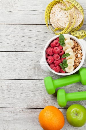 Photo for Healthy food and fitness concept. Breakfast cereal, fruits, nuts and sport equipment. Top view flat lay with copy space for your text - Royalty Free Image