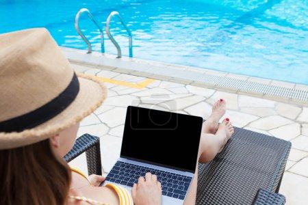 Photo pour Jeune femme utilisant un ordinateur portable pour le travail ou l'éducation près d'une piscine. Avec espace de copie pour votre texte ou application - image libre de droit