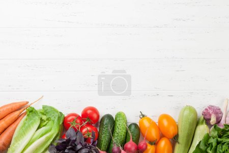 Photo for Assorted raw organic vegetables, herbs and spices. Fresh garden vegetarian food. Top view on wooden table with copy space - Royalty Free Image