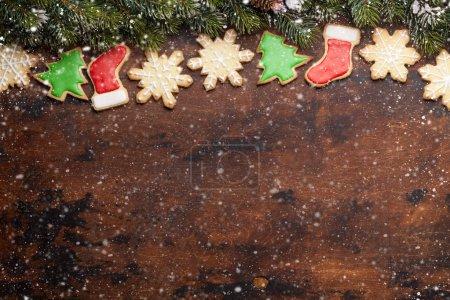 Foto de Tarjeta de felicitación navideña con galletas de pan de gingerbread y rama de árboles de xmas sobre fondo de madera. Vista superior con espacio para sus saludos. - Imagen libre de derechos