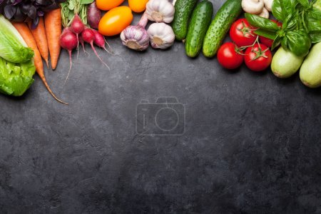 Photo for Assorted raw organic vegetables, herbs and spices. Fresh garden vegetarian food. Top view on stone table with copy space - Royalty Free Image