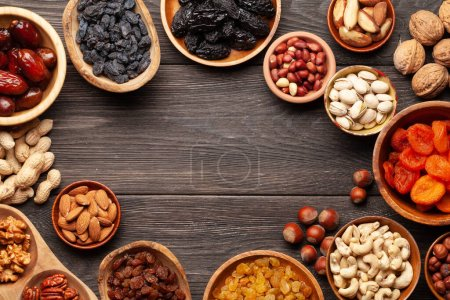 Photo for Various dried fruits and nuts on a dark wooden table. Top view flat lay with copy space - Royalty Free Image