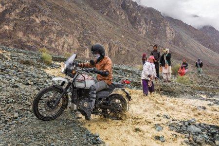 Nubra valley, India - June 29, 2017: Biker crossing river flowing from melting glacier in Himalaya mountains, Ladakh region, India