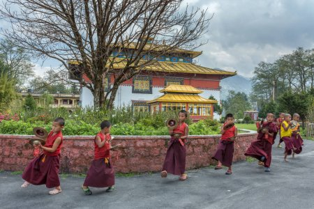 Gangtok, India - May 3, 2017: Unidentified young novice buddhist monks in traditional robes practicing in playing Tibetan music instrument tings ha in Tsuglakhang monastery