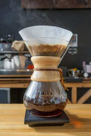 Close-up of brewing coffee in chemex on wooden table