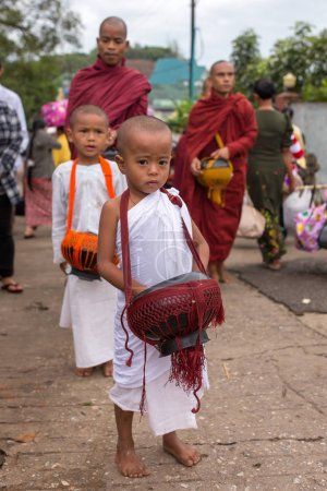 Kyaikhtiyo, Myanmar - October 16, 2016: Young buddhist novices and monks collecting everyday alms near the Kyaiktiyo pagoda or Golden rock, Myanmar.