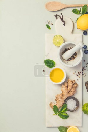Photo for Cooking ingredients on grey concrete background: olive oil, herbs and spices. Vegan food, vegetarian and healthily cooking concept. Top view - Royalty Free Image