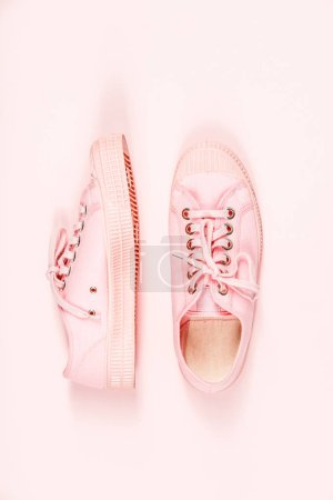Photo for Pair of pink canvas sneakers on pink background, top view, flat lay. Trendy fashion pastel Woman shoes. Copyspace - Royalty Free Image