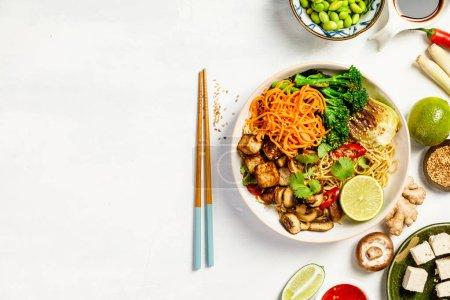 Photo for Vegetarian noodles with tofu, broccoli, mushrooms, carrot, bok choy on white stone table. Top view, flat lay, copyspace - Royalty Free Image