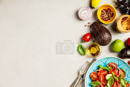 Photo for Tomato, basil, avocado and onion salad in blue plate for vegan, gluten free, allergy-friendly, clean eating or raw diet. Grey concrete background and top view - Royalty Free Image
