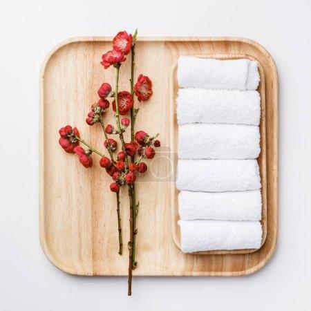 Foto de Concepto de tratamiento de spa, composición plana con toallas y flores de primavera sobre fondo blanco - Imagen libre de derechos
