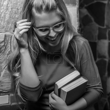 Young smiling beauty woman with books black-white portrait.