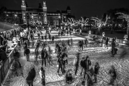 AMSTERDAM, THE NETHERLANDS - JANUARY 12, 2017: Many people skate on winter ice skating rink at night in front of the Rijksmuseum, a popular touristic destination in Amsterdam, The Netherlands.
