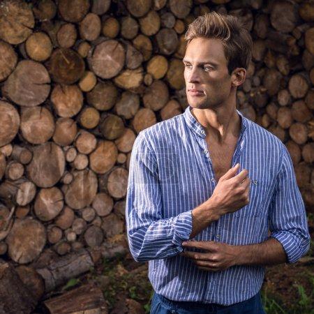 junger gutaussehender Mann in lässigem Hemd posiert vor hölzernem Hintergrund.