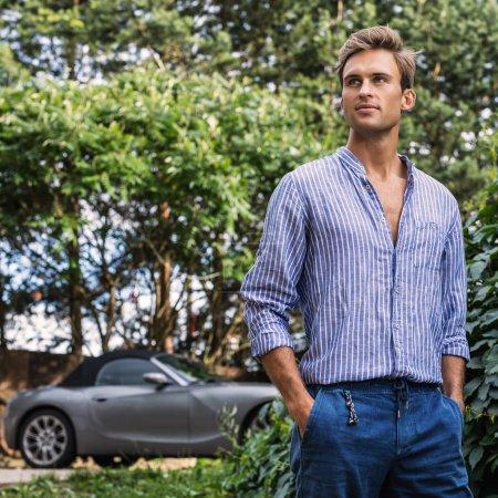 junger schöner Mann in lässiger Kleidung posiert im Sommergarten.