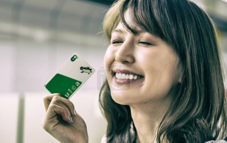 TOKYO - MAY 2016: Japanese girl happy with suica card. It is a prepaid smart card that allows you to use most public transport.