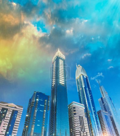 Downtown Dubai skyscrapers at night, skyward view.