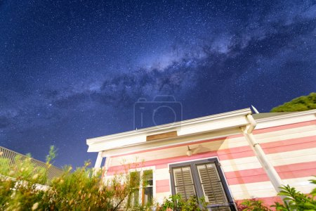 Pink house on a starry night with milky way.