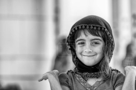 Portrait of young smiling muslim girl in the adras hijab headscarf or shawl visiting a mosque.