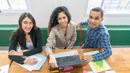 Photo for Group of smiling multi-ethnic coworkers sitting at the desk looking at the camera in the office. - Royalty Free Image