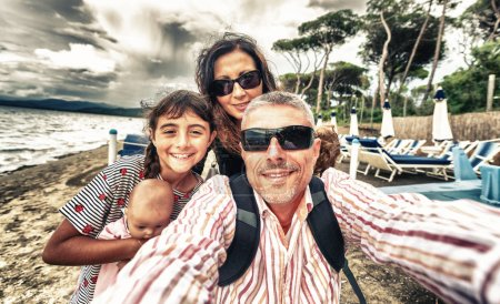 Photo for Family of three making selfie on the beach. Happy father, mother and daughter. - Royalty Free Image