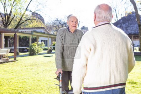 Photo for Seniors smiling and talking in nursing home garden. - Royalty Free Image
