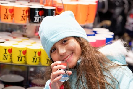 Photo for Happy smiling young girl visiting New York City in winter wearing hat and touching city souvenirs. - Royalty Free Image