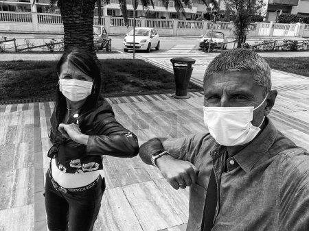 Photo pour Couple portant des masques maintenant la distance sociale en plein air toucher les coudes. - image libre de droit