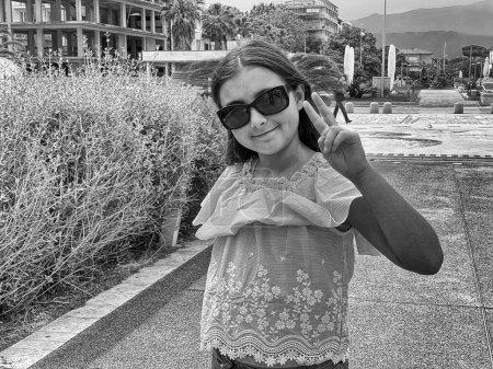 Photo pour Jeune fille faisant signe de victoire extérieur. - image libre de droit