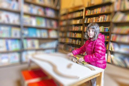 Photo for Cute young girl enjoying her time at the public library. - Royalty Free Image