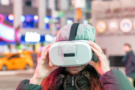 Photo for Woman wearing virtual reality goggles. Night city. New York city life, technology concept. - Royalty Free Image