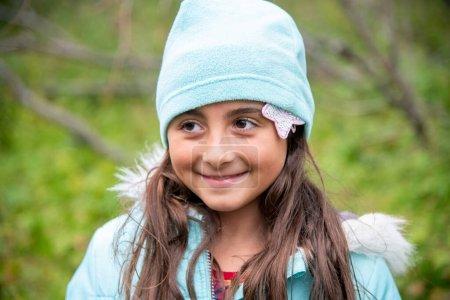 Photo pour Jolie jeune fille weraing chapeau pendant une journée froide en plein air. Sourire à quelqu'un. - image libre de droit