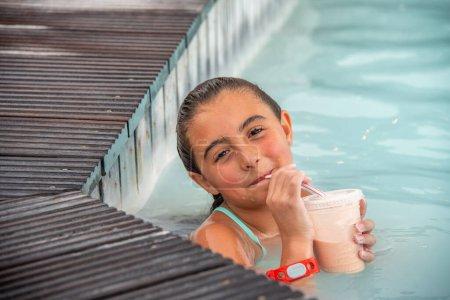Photo pour Jolie fille boire une tasse de jus de fruits dans la piscine. - image libre de droit
