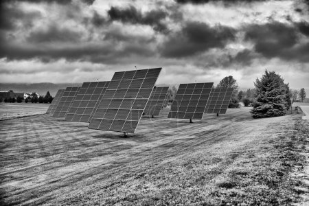 Photo for Solar panels at sunrise with cloudy sky in the countryside. Solar energy, modern electric power production technology, renewable energy concept. Environmentally friendly electricity production. - Royalty Free Image