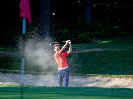Photo for Young golf player hitting ball by wood during competition - Royalty Free Image
